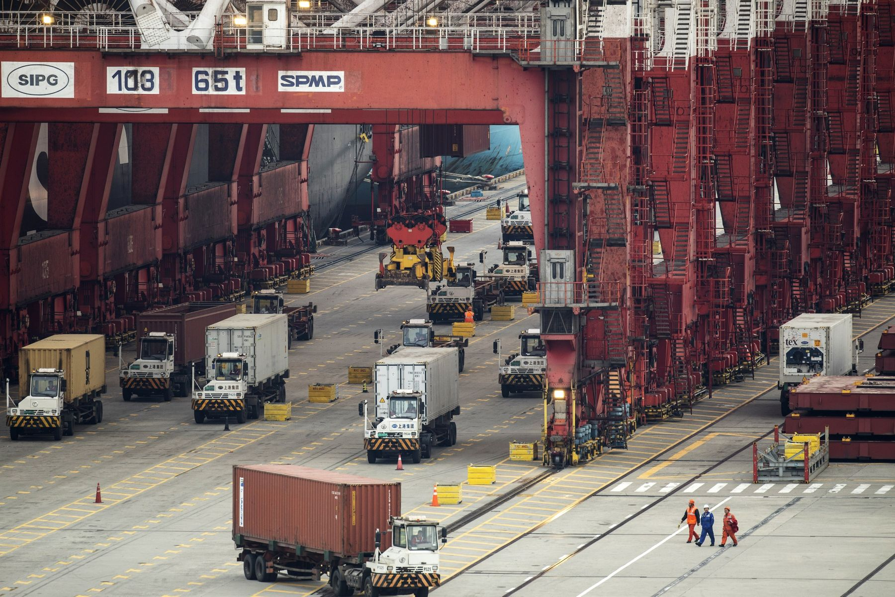 Vehicles travel under gantry cranes at the Yangshan Deepwater Port in Shanghai, China.