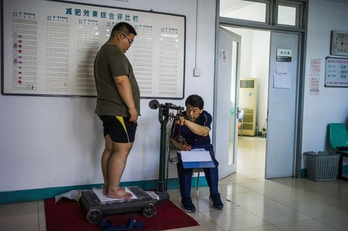 An overweight boy gets his weight checked at a hospital in Tianjin