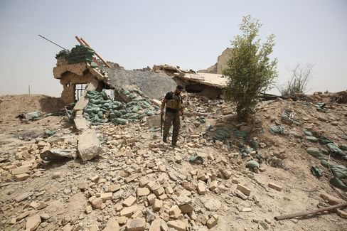 A member of the Iraqi government forces walks amid the rubble of a destroyed building on the front line near the village of al-Azraqiyah, northwest of the city of Fallujah, on June 5, 2016.