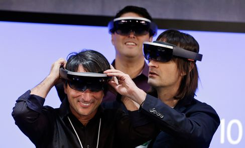 Microsoft's Joe Belfiore, left, tries on a HoloLens device with colleagues Alex Kipman, right, and Terry Myerson following an event demonstrating new features of Windows 10 at the company's headquarters on Jan. 21, 2015, in Redmond, Washington.