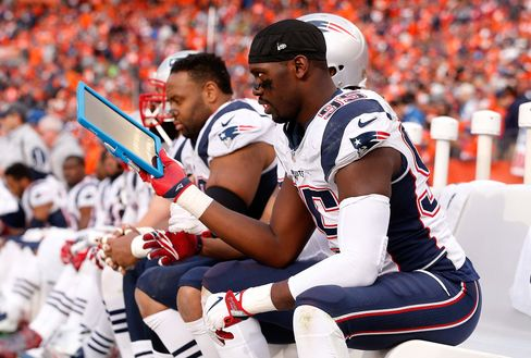 Chandler Jones #95 of the New England Patriots holds a Microsoft Surface tablet on the sideline in the third quarter against the Denver Broncos in the AFC Championship game at Sports Authority Field at Mile High onJan.24, 2016 in Denver, Colo.