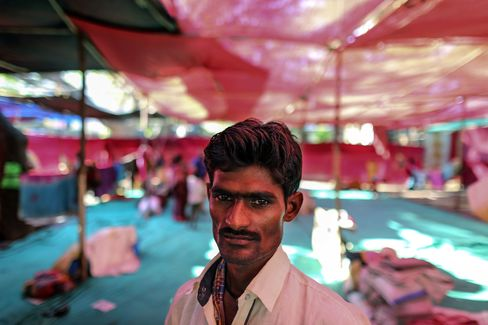 Migrant farmer Vijay Jadhav stands for a photograph inside a temporary shelter in Thane, India.