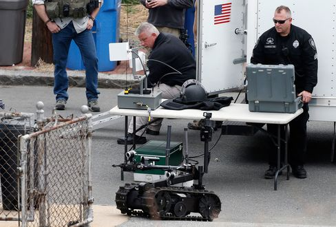 A member of the Cambridge police bomb squad, right, deploys a robot during the search for a suspect in the Boston Marathon bombings in Cambridge, Mass. on April 19, 2013.