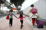 A migrant mother walks with childrenin Tijuana, Mexico.