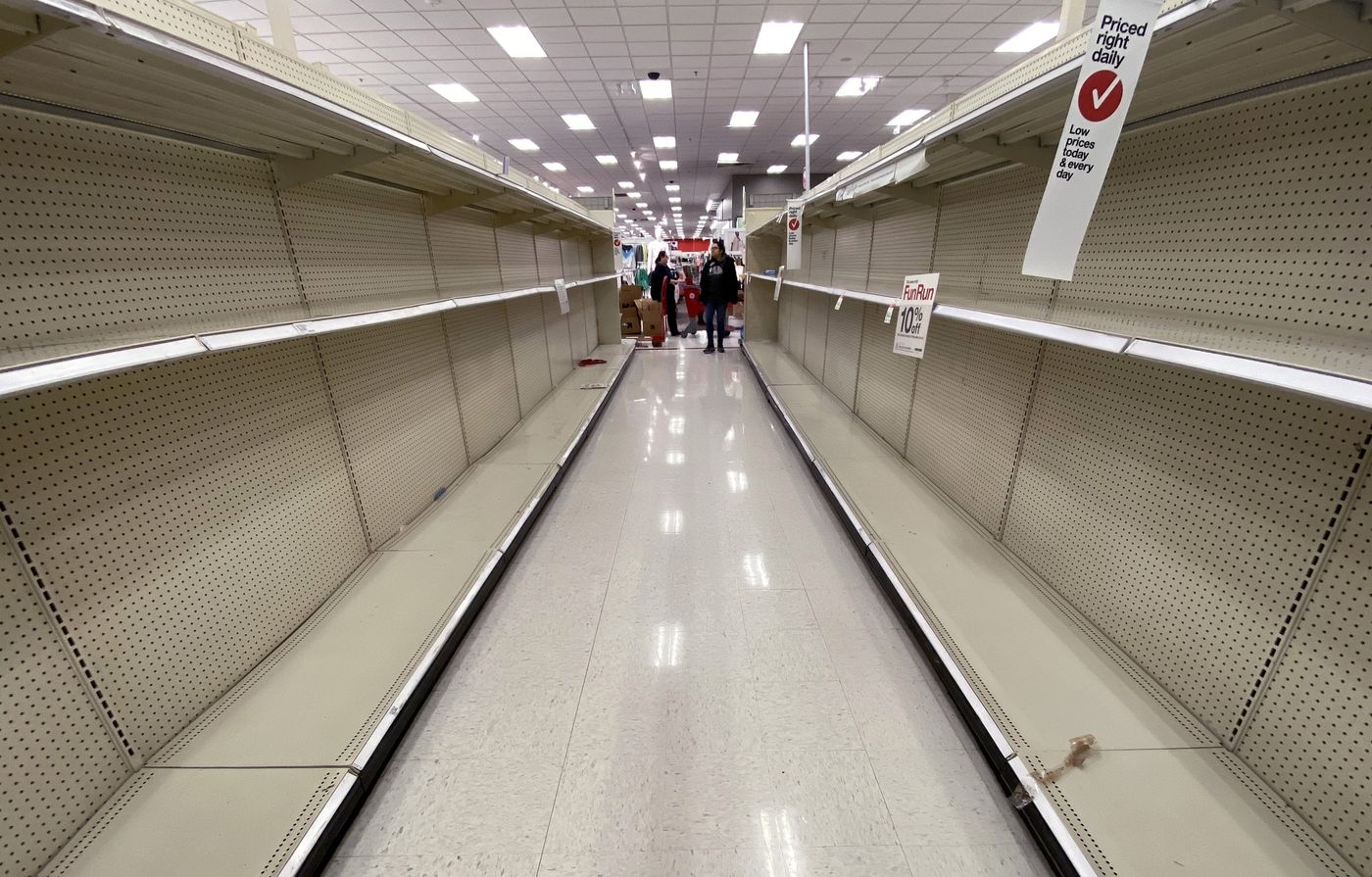 Shelves normally stocked with hand wipes, hand sanitizer and toilet paper sit empty at a Target store in Arlington, Virginia, on March 13, 2020.