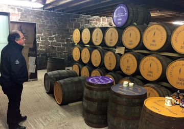David Thomson surveys the casks of Scotch aging in Annandale's bonded warehouse.
