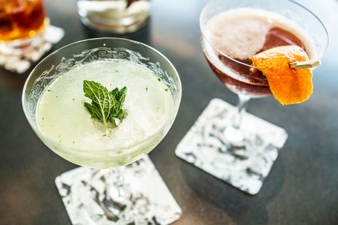 """The mint colored """"South Side"""" is made with 2oz Knickerbocker Gin, 1oz lime juice and 1.5oz of mint simple syrup. The cherry-colored """"Blood & Sand"""" is a mix of 1oz Dewars scotch, 1oz Cherry Heering, 1oz Noilly Pratt sweet vermouth and 1oz blood orange juice. Each are served in etched vintage coupe glasses."""