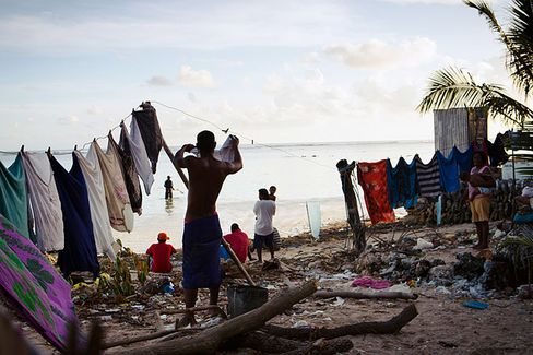 A man hangs out his laundry in Tarawa's Bairiki Village, one of the most high-density slum areas in Kiribati