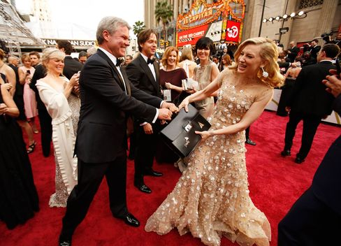 Cate Blanchett playfully tugs at the briefcase held by PwC's Brian Cullinan as she arrives at the 86th Annual Academy Awards on March 2, 2014, at the Dolby Theatre in Hollywood, Calif.