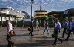 Commuters walk past the Circular Quay wharf in Sydney, Australia.