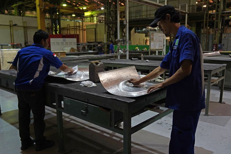Workers handle Airbus A350 components. Image: Dimas Ardian/Bloomberg