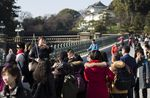 A tour guides speaks to Chinese tourists in the grounds of the Imperial Palace in Tokyo, Japan.