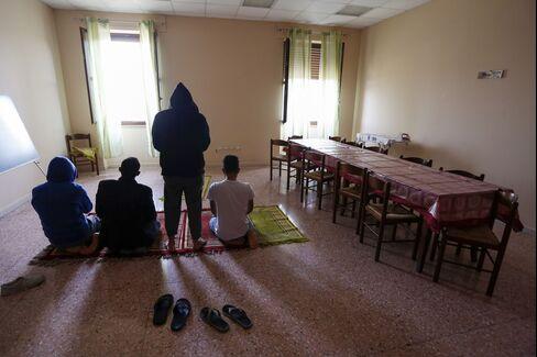 A group of refugees pray at the Palazzo Condo