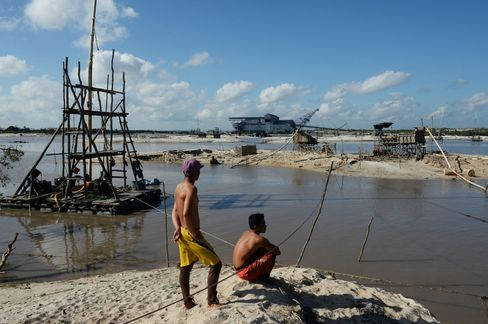 Workers stand next to mining pits in central Bangka Island, Indonesia. Photographer: Dimas Ardian/Bloomberg
