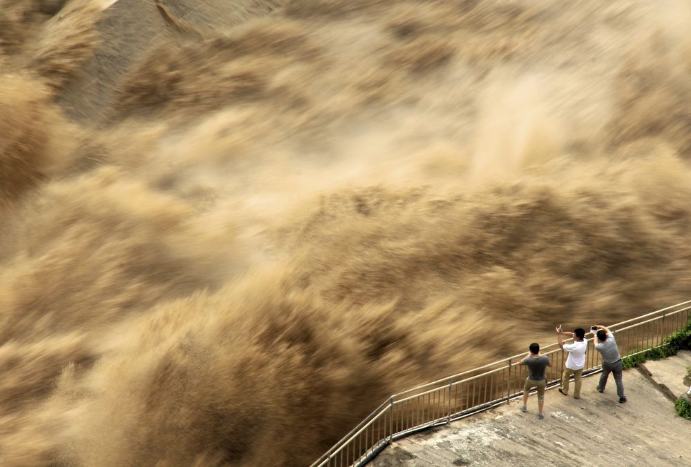People view water gushing out of Sanmenxia Dam in Sanmenxia city, central China's Henan province on June 30.