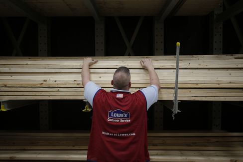 A Worker Stacks Wood at a Lowe's Store