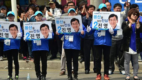 Supporters of the opposition Minjoo Party hold placards of the party's local candidate Chin Young.