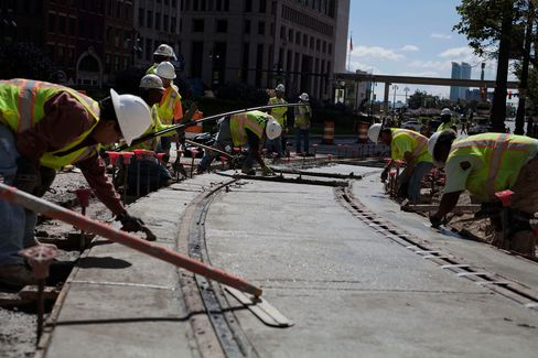 Workers put the finishing touches on a section of the M-1 Rail line in Detroit during construction in 2015. It was the first public transit project in Detroit to bring together both public and private funding for its construction.