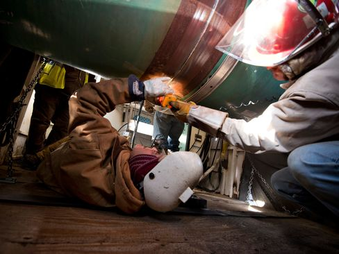 Workers inspect a weld on the joint between two sections of pipe on a Gulf Coast Project pipeline in Atoka, Oklahoma.