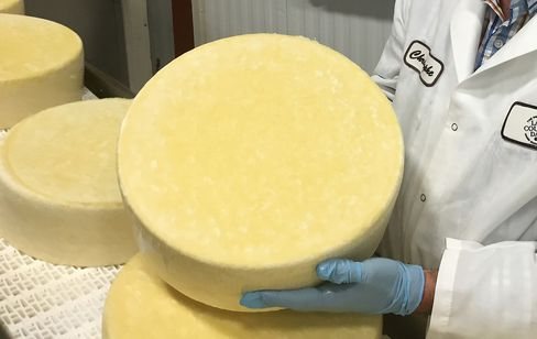 A cheese maker for Arthur Schuman Inc. holds a round of cheese in Turtle Lake, Wisconsin.