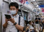 Commuters wearing face masks travel on a train in Tokyo.