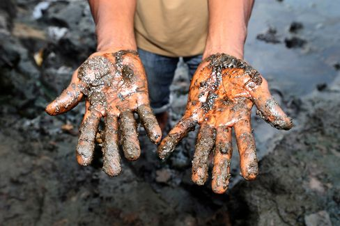Eric Dooh shows the oil polluted mud in Goi.