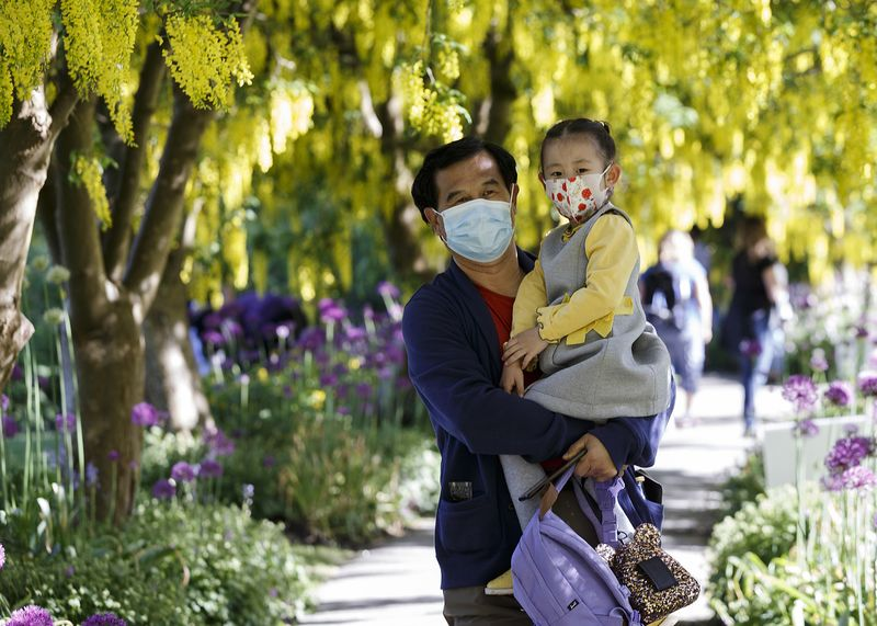 A man carries a child on a one way walk through Laburnum Walk in Vancouver on May 15.