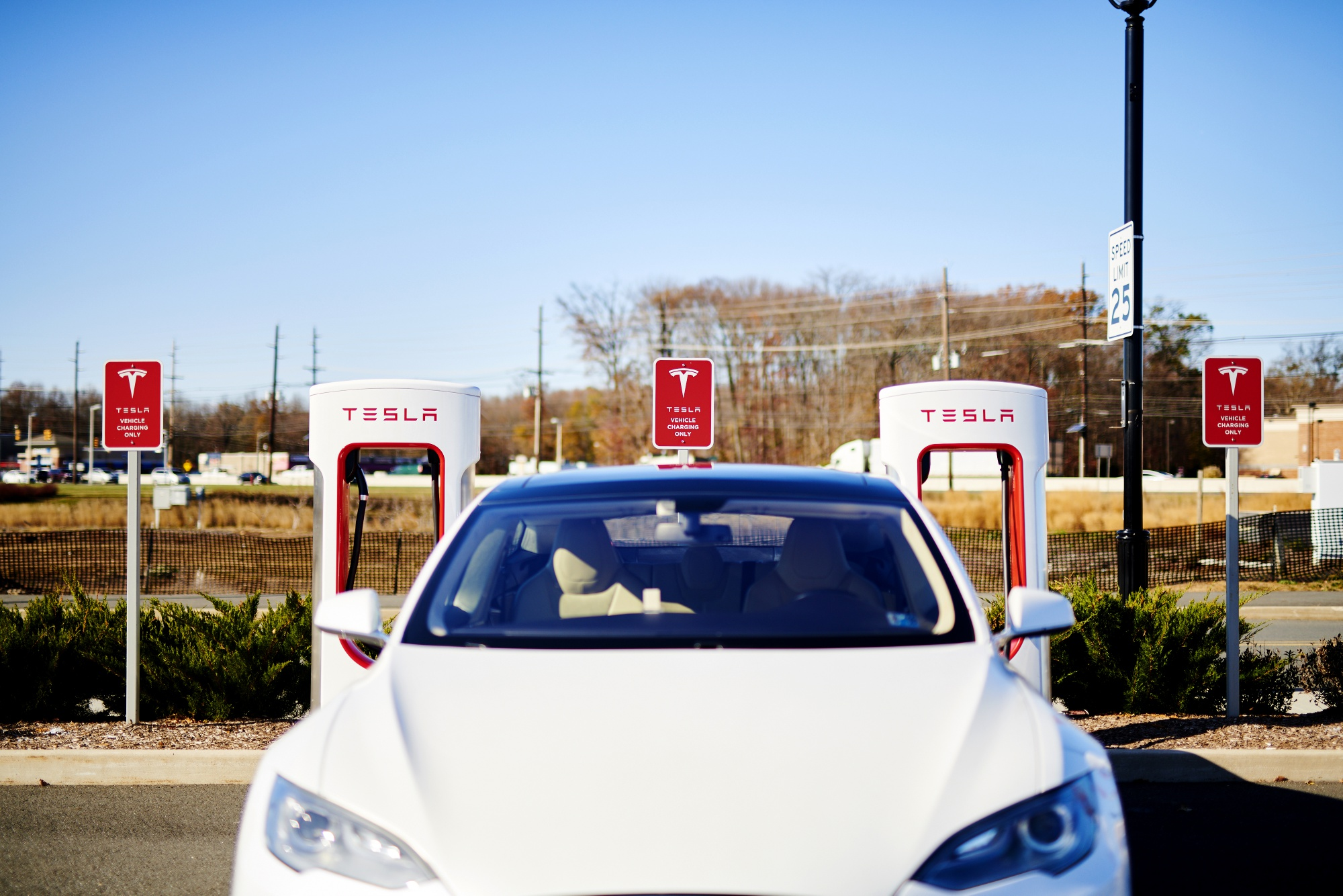 A Tesla Inc. electric vehicle sits parked in front of a charging station.