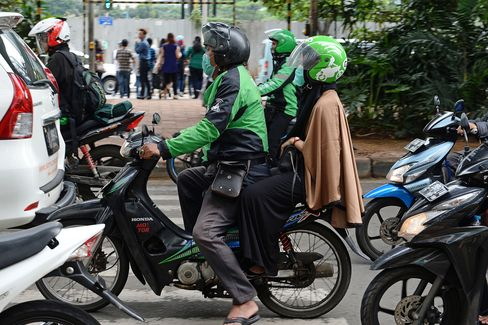 A Go-Jek rider drives a customer through the streets of Jakarta.