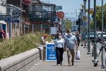 People wearing protective masks walk on Jefferson Street on Fisherman's Wharf in San Francisco, California, U.S.
