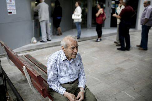 A pensioner sits on a bench beside customers waiting to use an automated teller machine (ATM), outside a National Bank of Greece SA bank branch in Thessaloniki, Greece, on Saturday, June 27, 2015.