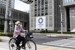 A cyclist travels past a banner featuring the emblem for the Tokyo 2020 Olympic Games displayed outside the Tokyo Metropolitan Government Building in Tokyo, Japan, on Friday, June 18, 2021.