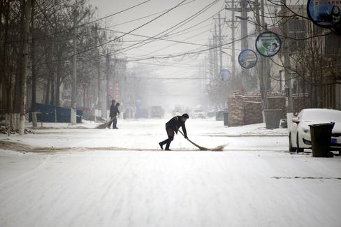People clean up snow in the street in the town of Jiazhai in Liaocheng on Jan. 22.