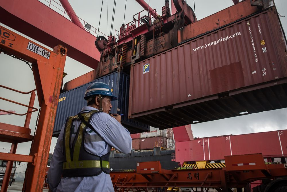 An employee observes a shipping container being lifted by a gantry crane at the Port of Kaohsiung in Kaohsiung, Taiwan.
