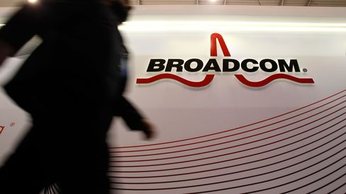 An attendee passes the Broadcom Corp. pavilion on day two of the Mobile World Congress in Barcelona, Spain, on Feb. 25, 2014.