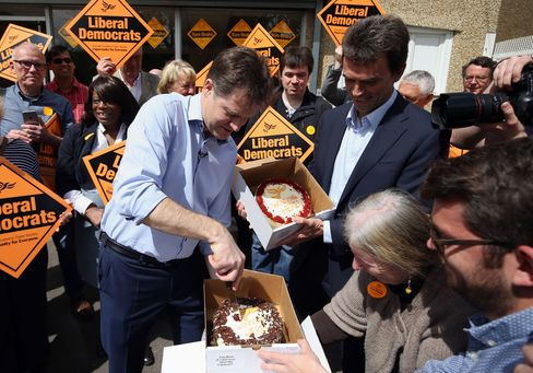Liberal Democrat Party Leader Nick Clegg cuts cake during a visit to Carshalton in London, on May 4, 2015.