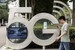 An employee using a smartphone walks past a sign for the 5G Park at the Huawei Technologies Co. headquarters in Shenzhen, China.