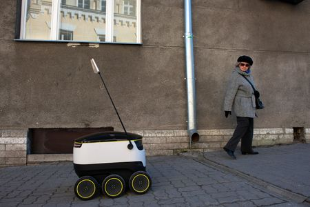 A pedestrian does a double take as a prototype Starship Technologies self driving delivery robot travels along a sidewalk in Tallinn, Estonia.