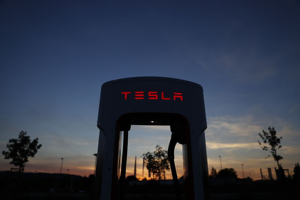 15c7eb39485 A Tesla Inc. Supercharger station stands illuminated at dusk in Rubigen,  Switzerland.