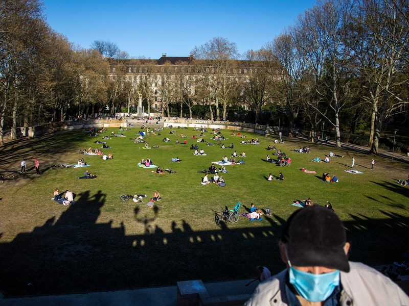 Sunbathers liein the park next to Schoeneberg town hall in Berlin on April 18.
