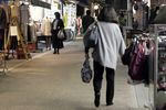 Pedestrians and shoppers walk through the Yanaka Ginza shopping street at dusk in the Yanesen district of Tokyo, Japan.