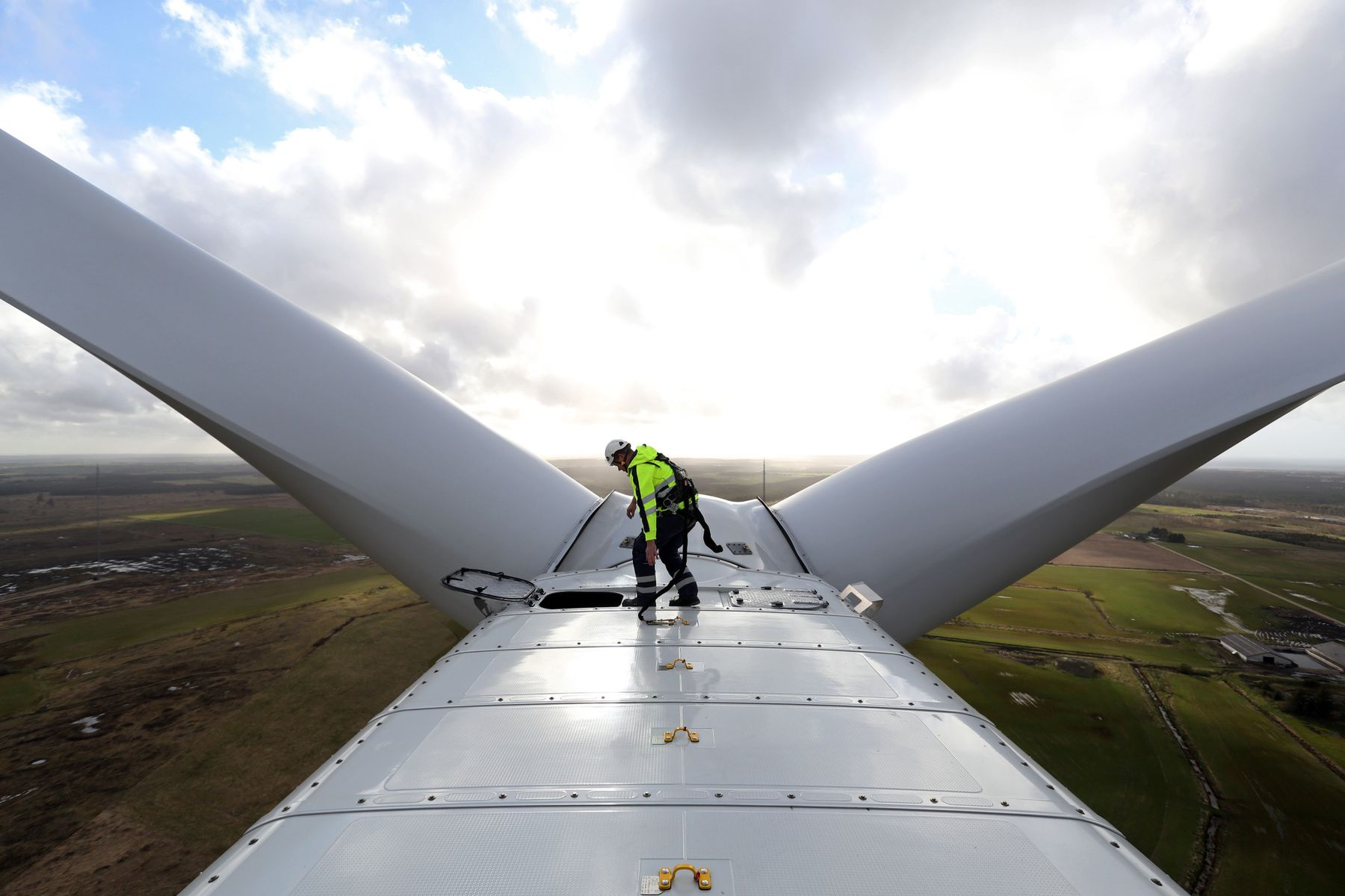 An employee prepares to exit the nacelle of a Vestas V136 wind turbine in Osterild, Denmark.