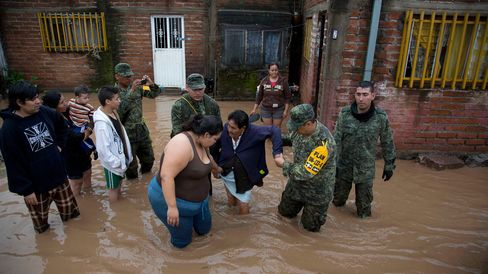 Soldiers help a woman to leave her flooded house in Zoatlan, Nayarit state, Mexico, on Oct. 24.