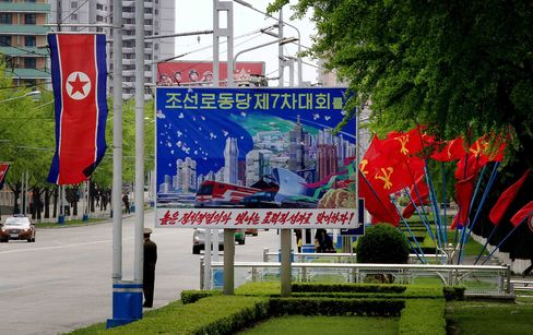 A street is decorated with the national flag of North Korea and signs.