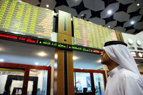 An investor monitors electronic stock boards at the Dubai Financial Market.