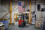 An American flag hangs above a worker operating a forklift at a manufacturing facility in Virginia Beach, Virginia.