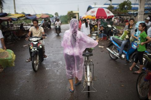 A woman pushes her bicycle past a market in a garment manufacturing district in Phnom Penh, Cambodia.