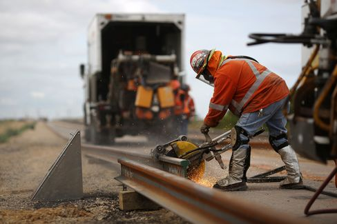 A maintenance-of-way worker saws through a piece of rail, in Alva, Okla., on Aug. 19.