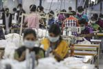 Employees use sewing machines on a production line at a factory in Tiruppur, Tamil Nadu.