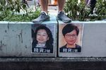 A demonstrator stands above posters featuring Hong Kong Chief Executive Carrie Lam, right, and Hong Kong Secretary for Justice Teresa Cheng in Hong Kong.
